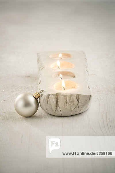 Advent decoration,  four lighted candles,  and silvery christmas tree ball,  studio shot