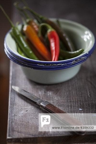 Grüne und rote Chilischoten in kleiner Schüssel und Messer auf Holztisch  Studioaufnahme