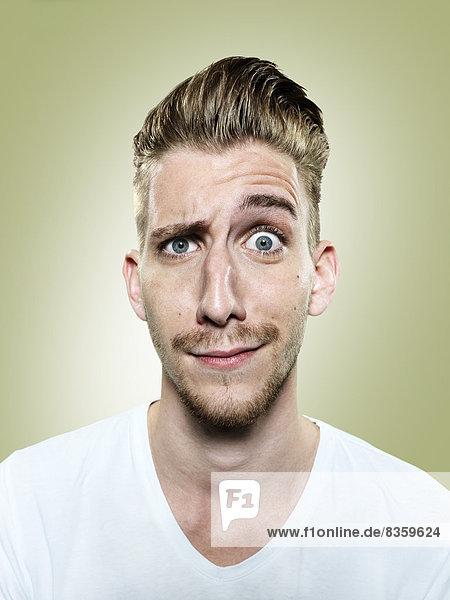 Portrait of doubtful young man  studio shot