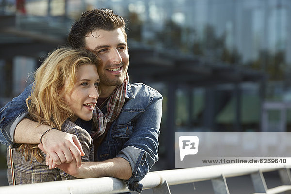 Germany  Dusseldorf  Young couple embracing  leaning on railing