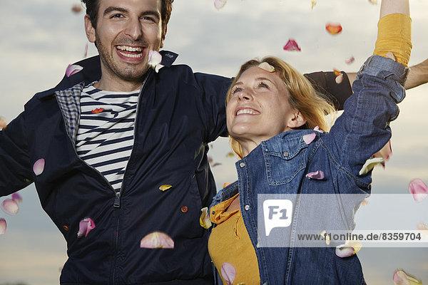 Deutschland  Düsseldorf  Junges Paar wirft Blütenblätter