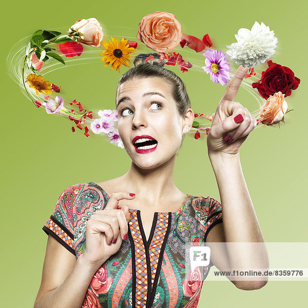 Young woman with flying flowers around her head  Composite