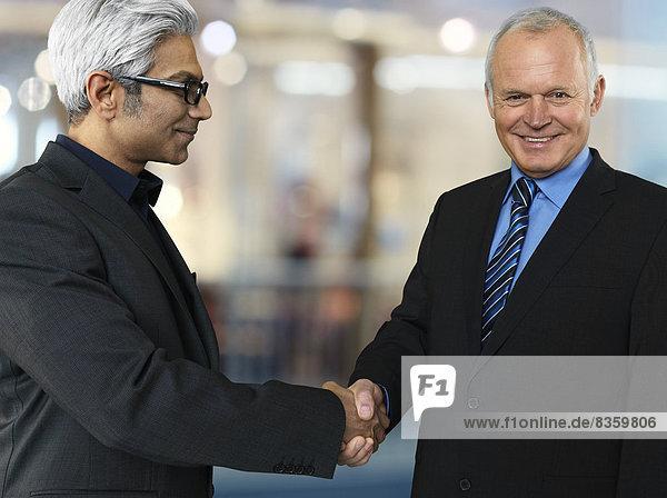 Portrait zweier Geschäftspartner beim Händeschütteln