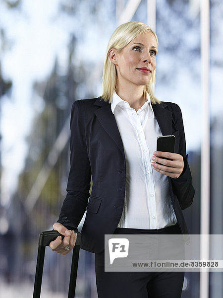 Portrait of business woman with luggage and smart phone