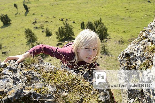 Junge klettert auf einem Felsen