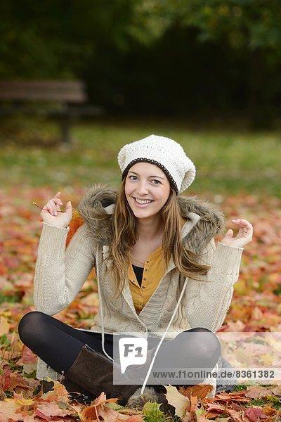 sitzend junge Frau junge Frauen lächeln Laub