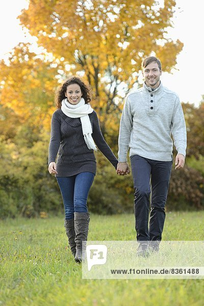 Lächelndes Paar geht im Herbst spazieren