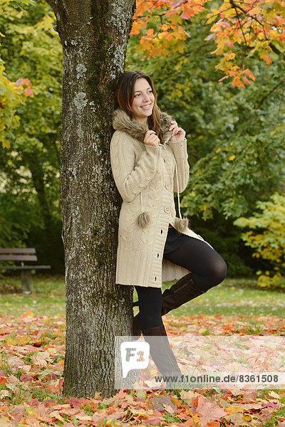Lächelnde junge Frau steht an einem Baum im Herbst