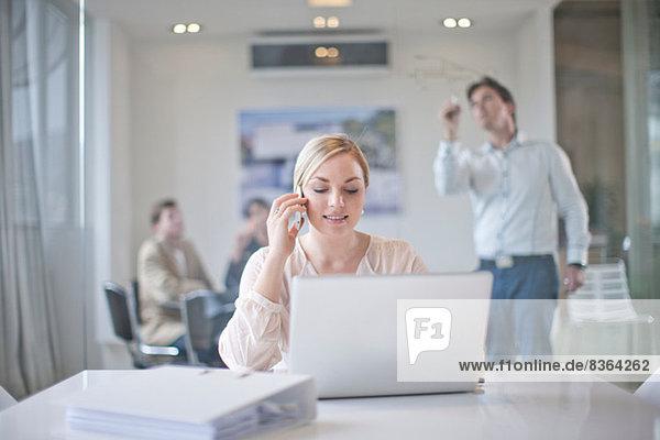 Frau sitzt am Konferenztisch mit Laptop und Handy  Kollegen arbeiten im Hintergrund