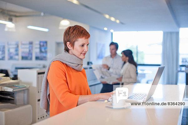 Geschäftsfrau am Tisch sitzend mit Laptop