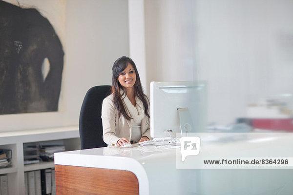 Geschäftsfrau am Schreibtisch sitzend am Computer