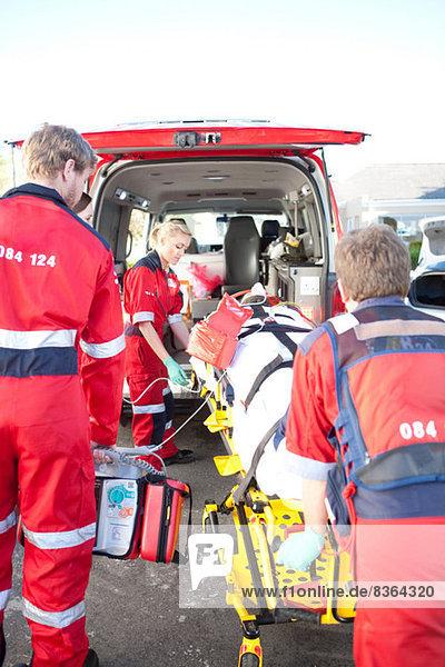 Rettungssanitäter heben Frau auf Trage in den Krankenwagen