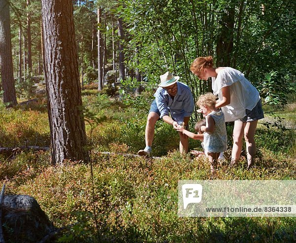 Parents and daughters exploring in forest