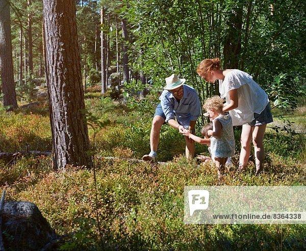 Eltern und Töchter auf Entdeckungsreise im Wald
