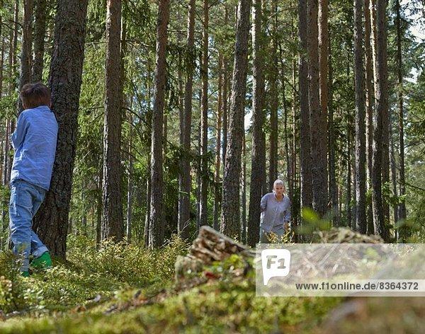 Mutter und Sohn beim Verstecken im Wald