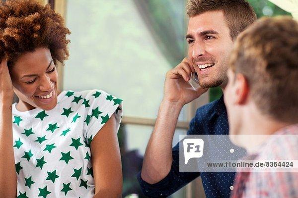 Drei Freunde lachen  Mann am Smartphone