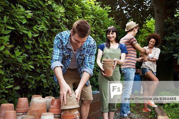 Vier Freunde beim Stapeln von Terrakotta-Pflanzentöpfen