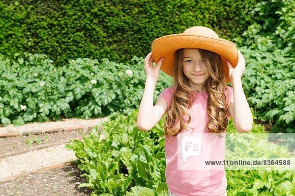 Mädchen mit Strohhut im Garten