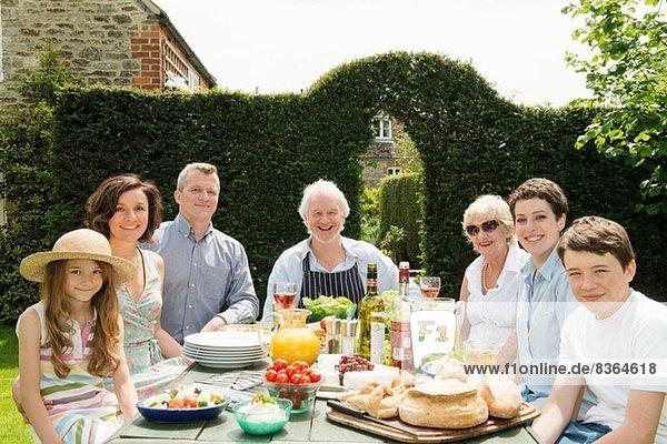 Porträt einer Familie von drei Generationen beim Mittagessen im Freien