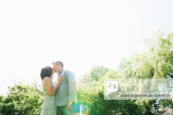 Reife Paare beim Küssen im Garten