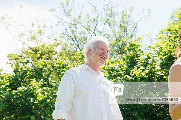 Älterer Mann in weißem Hemd  lachend