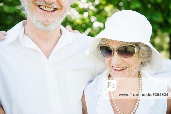 Porträt einer älteren Frau mit Sonnenbrille und weißem Sonnenhut