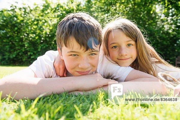 Portrait von Bruder und Schwester auf Gras liegend