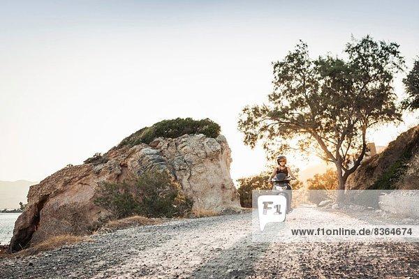 Frau beim Mopedfahren entlang der Küste bei Pythagorio  Samos  Griechenland