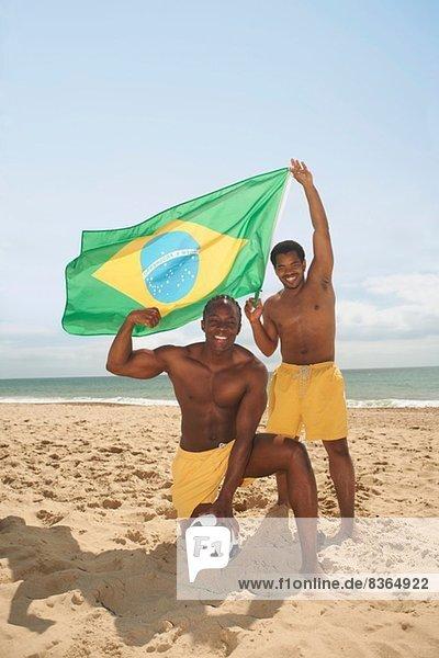 Männer posieren mit brasilianischer Flagge am Strand