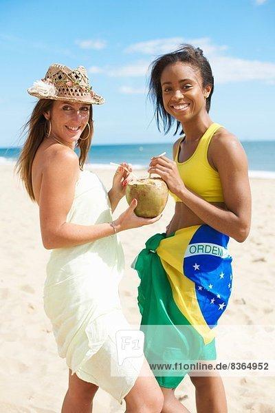 Frauen teilen sich Kokosnusswasser