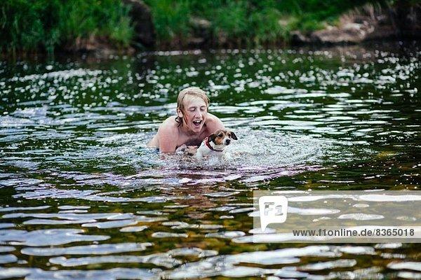 Junger Mann und sein Hund spielen im Fluss