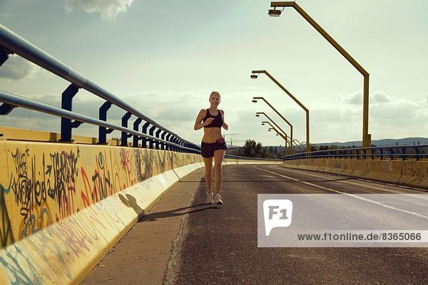 Young female jogger running on bridge