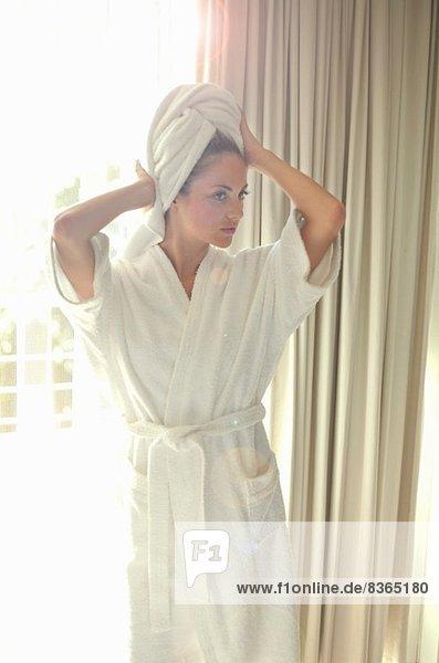 Junge Frau in Bademantel mit Handtuch umwickelten Haaren