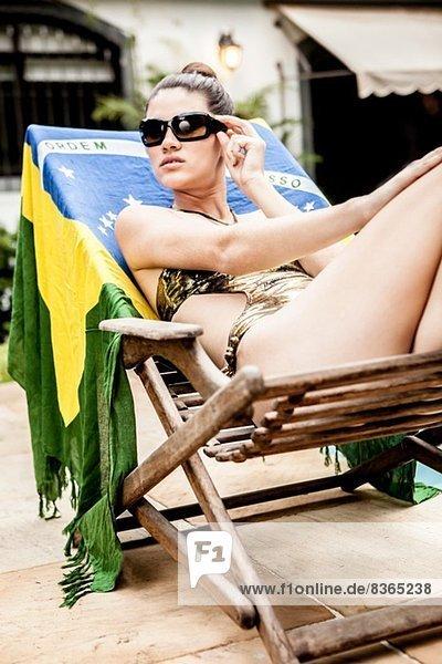 Junge Frau auf Hotel-Liege mit Sonnenbrille