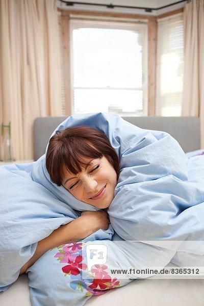 Junge Frau in Bettdecke gehüllt