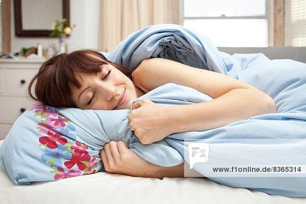 Junge Frau im Bett mit geschlossenen Augen