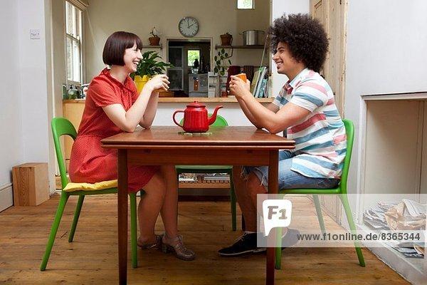 Junges Paar am Küchentisch sitzend