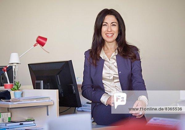 Geschäftsfrau im Anzug am Schreibtisch sitzend
