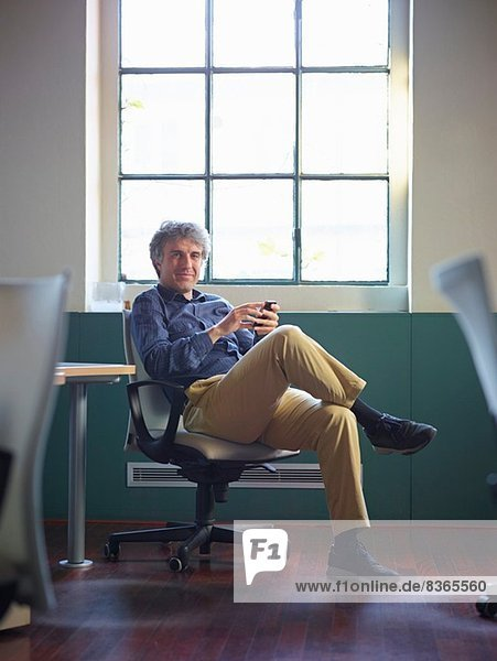 Erwachsener Geschäftsmann sitzt auf Bürostuhl mit Handy