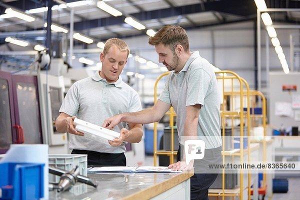 Arbeiter diskutieren über Bauteil in der Maschinenfabrik