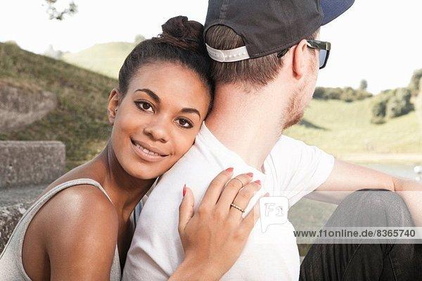 Junge Frau umarmt Freund