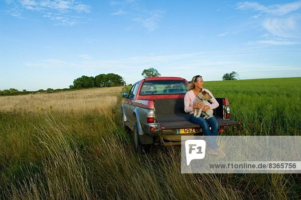 Frau sitzt auf dem Rücksitz eines Pick-up auf einem Feld und hält einen Hund.