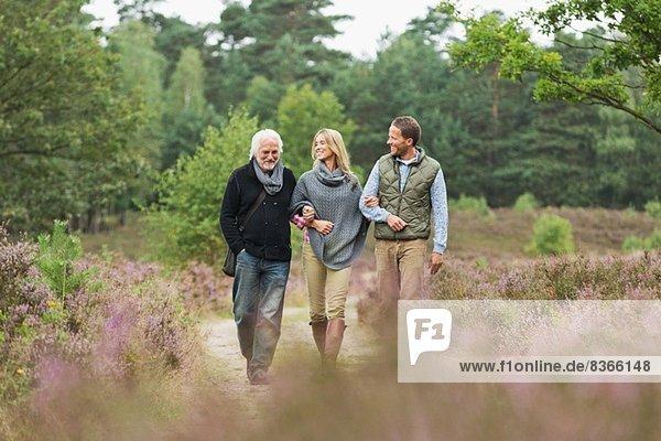 Älterer Mann  mittlerer erwachsener Mann und Frau  die durch den Wald gehen