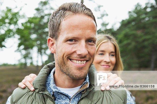 Porträt eines erwachsenen Mannes mit Blick auf die Kamera  Frauenhände auf den Schultern