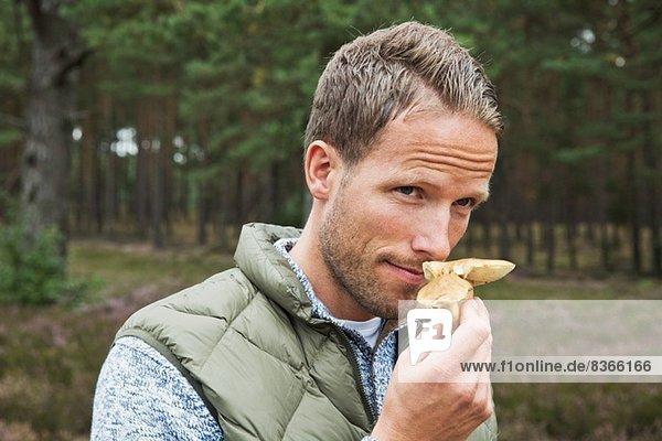 Mid adult man smelling mushroom