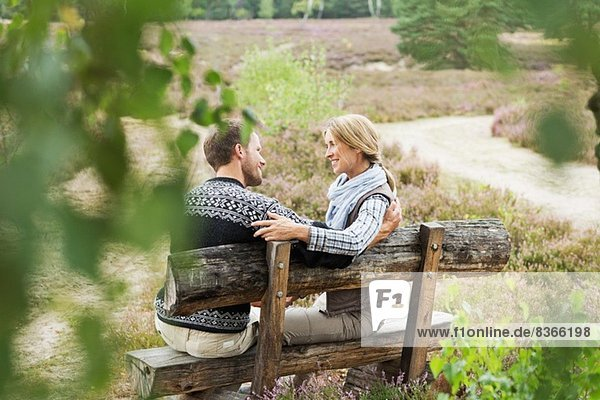 Mittleres erwachsenes Paar auf Holzbank