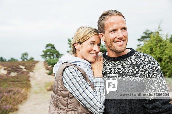 Mittleres erwachsenes Paar schaut weg  lächelnd