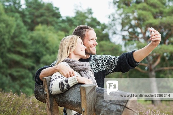Mid adult couple on bench photographing themselves