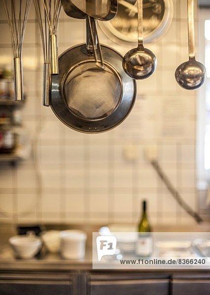 In der Großküche hängende Metallgeräte