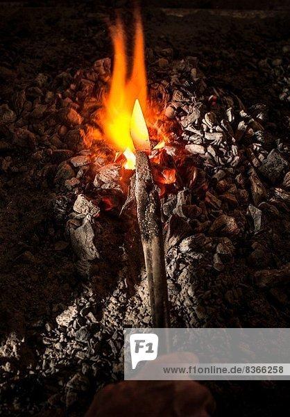 Schmied hält Metallmesser im Ofen